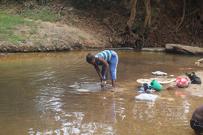Water: Carrying the Burden - Woman Washing Dishes in Dirty Water