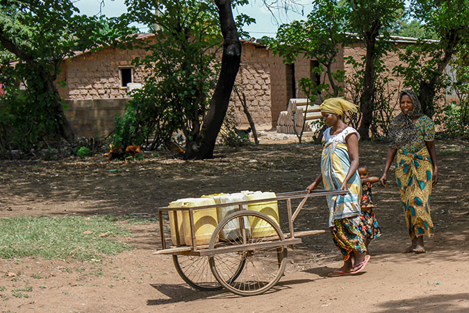 Water: Carrying the Burden - Woman Carting Water Containers