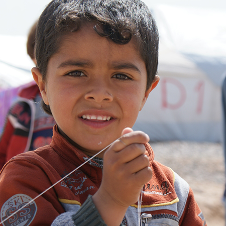 Critical Aid: Refugee Boy Recipient of Supplies