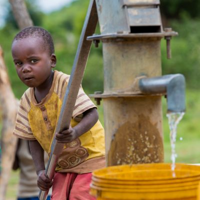Small Boy Fills Bucket from Water Well